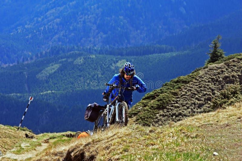 Hombre joven que empuja su bici encima de la montaña foto de archivo libre de regalías
