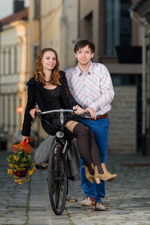 Hombre joven que empuja a su novia en la bicicleta fotografía de archivo