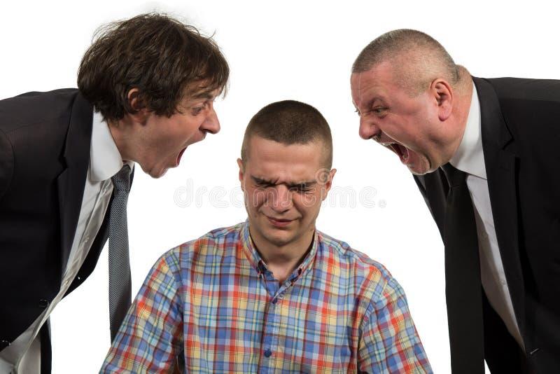 Hombre joven que es gritado en el encargado de sexo masculino de cerca de dos mayores en blanco imágenes de archivo libres de regalías