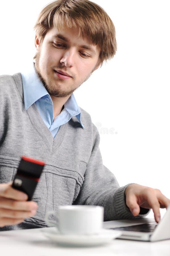 Hombre joven que escribe el mensaje corto en el teléfono celular fotografía de archivo libre de regalías