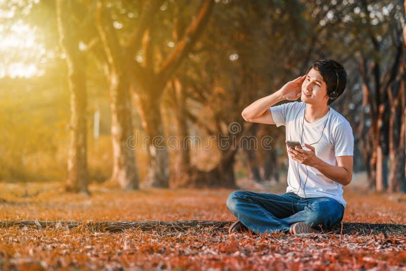 Hombre joven que escucha la música con los auriculares del móvil en parque fotografía de archivo libre de regalías