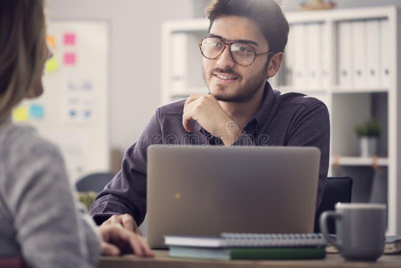 Hombre joven que escucha un cliente en la oficina imagenes de archivo