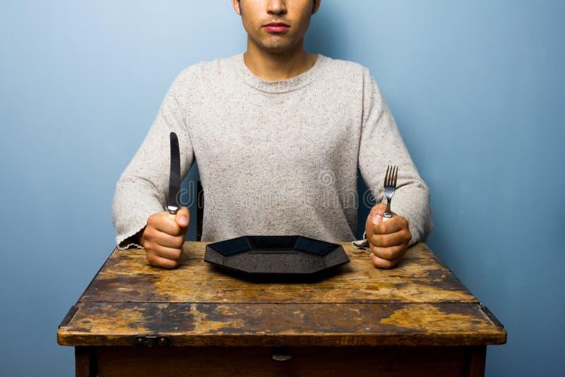 Hombre joven que espera su cena foto de archivo