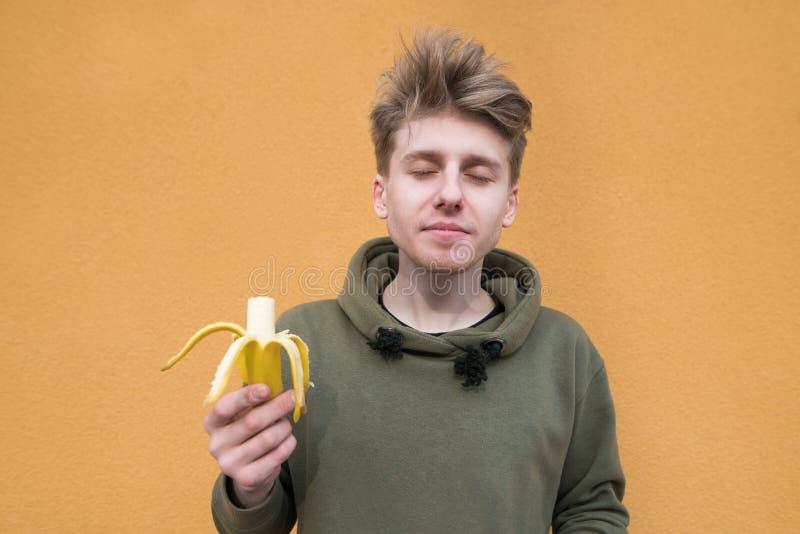 hombre joven que está gozando del bocado del plátano Un plátano delicioso para el almuerzo en el fondo de una pared anaranjada imagenes de archivo
