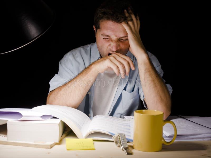 Hombre joven que estudia en la noche imagen de archivo