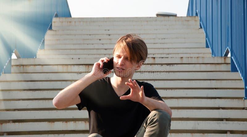 Hombre joven que explica algo complicado, mientras que habla a través del teléfono, sentándose en las escaleras con la cerca azul foto de archivo libre de regalías
