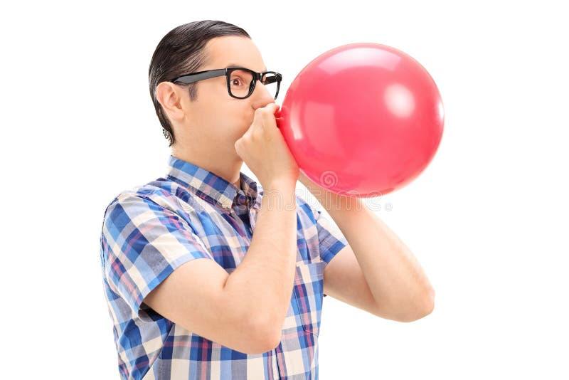 Hombre joven que explota un globo foto de archivo libre de regalías