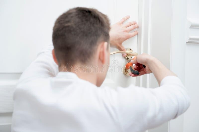 Hombre joven que fija el tirador de puerta fotografía de archivo
