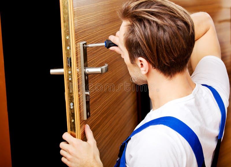 Hombre joven que fija la puerta con destornillador foto de archivo