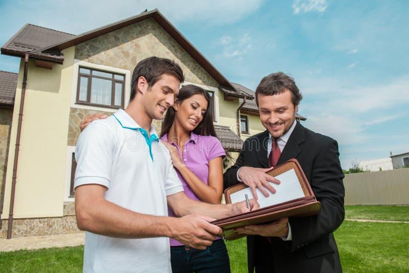 Hombre joven que firma alquilando el contrato con el agente inmobiliario imágenes de archivo libres de regalías