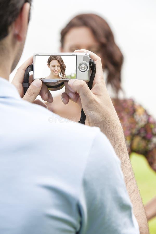 Hombre joven que fotografía a la mujer a través de la cámara digital en parque imagen de archivo