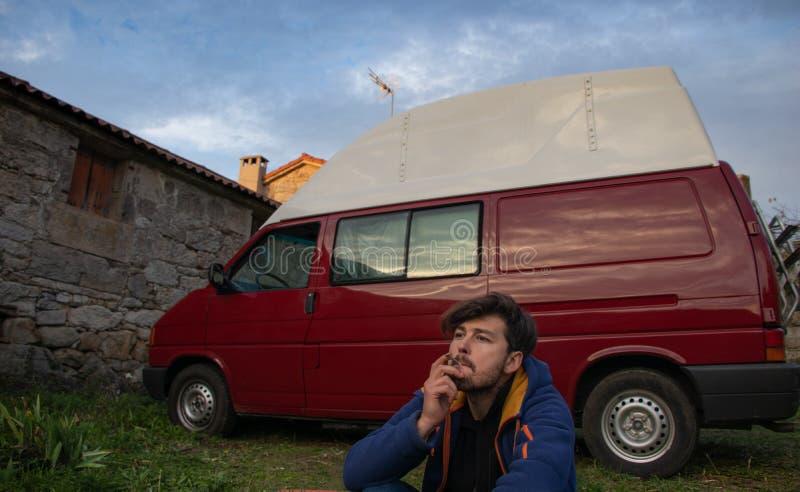 Hombre joven que fuma delante de su autocaravana roja fotografía de archivo