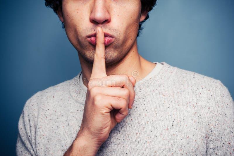 Hombre joven que gesticula silencio con el finger en los labios imagen de archivo libre de regalías