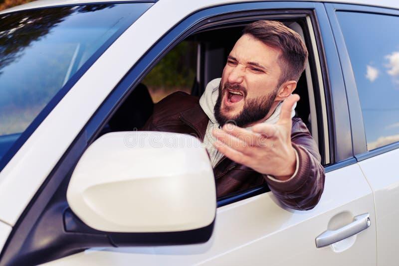 Hombre joven que grita de la ventana de su coche imágenes de archivo libres de regalías