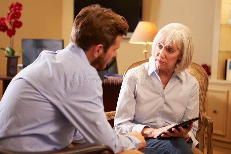 Hombre joven que habla con el consejero que usa la tableta de Digitaces fotos de archivo libres de regalías