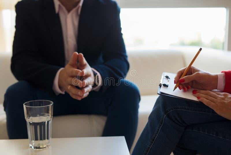 Hombre joven que habla con el terapeuta imágenes de archivo libres de regalías