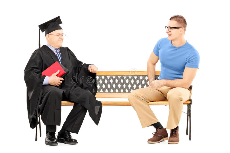 Hombre joven que habla con un profesor de la universidad asentado en banco imágenes de archivo libres de regalías