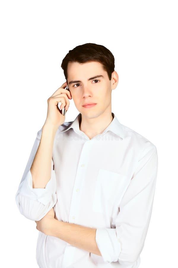 Hombre joven que habla en el teléfono aislado fotografía de archivo