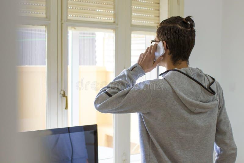 Hombre joven que habla en el teléfono en casa imagenes de archivo