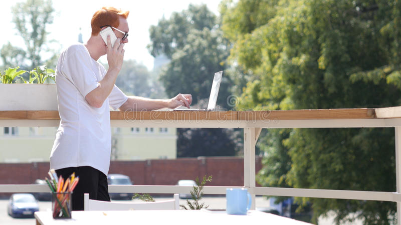 Hombre joven que habla en el teléfono, colocándose en el balcón al aire libre foto de archivo