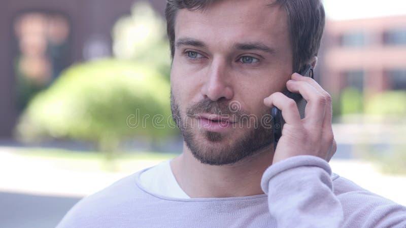 Hombre joven que habla en el teléfono, negociando en buen humor fotos de archivo libres de regalías