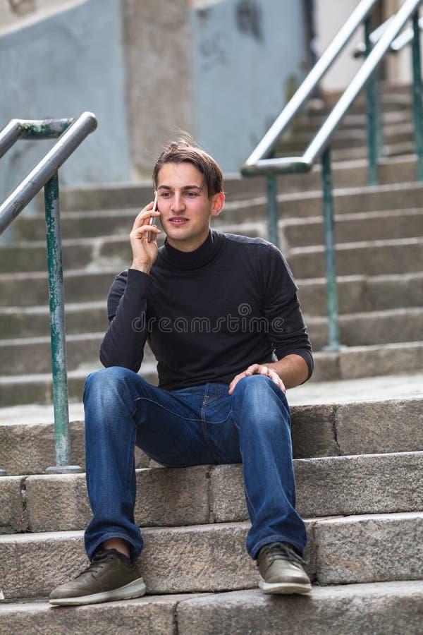 Hombre joven que habla en el teléfono que se sienta en las escaleras imagenes de archivo