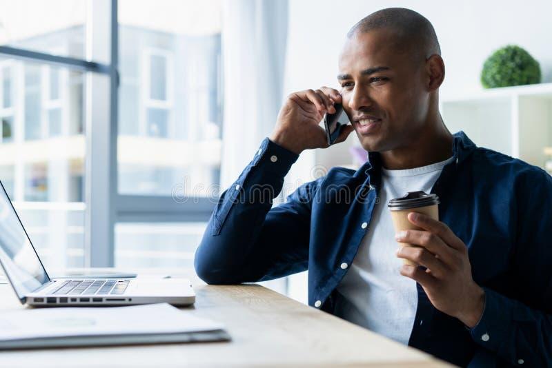 Hombre joven que habla en su teléfono móvil en oficina Sentada ejecutiva africana en su escritorio con el ordenador portátil foto de archivo libre de regalías