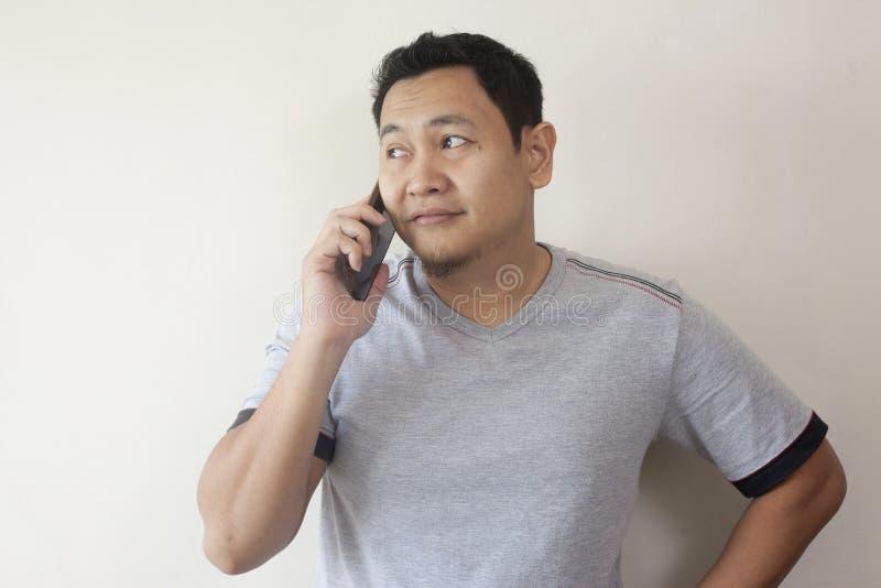 Hombre joven que habla en su tel?fono, risa sonriente feliz imagen de archivo libre de regalías