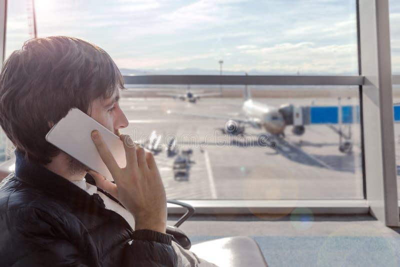 Hombre joven que habla por el teléfono móvil en pasillo del aeropuerto mientras que hola está esperando el avión de embarque foto de archivo libre de regalías