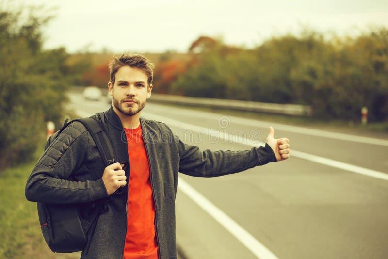 Hombre joven que hace autostop fotografía de archivo