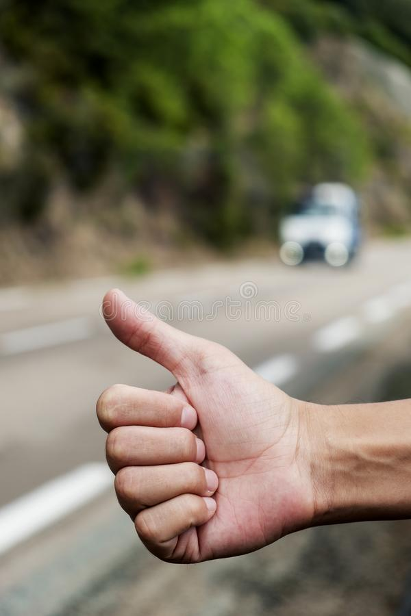 Hombre joven que hace autostop imagen de archivo libre de regalías