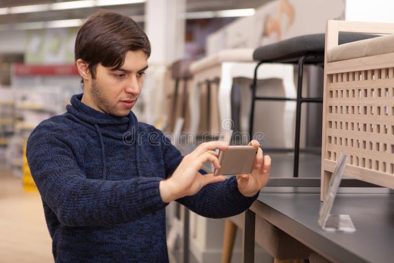 Hombre joven que hace compras en casa tienda de equipamiento imagen de archivo