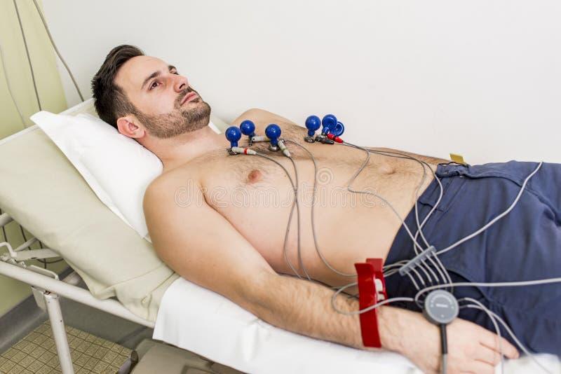 Hombre joven que hace ECG en hospital imagen de archivo libre de regalías