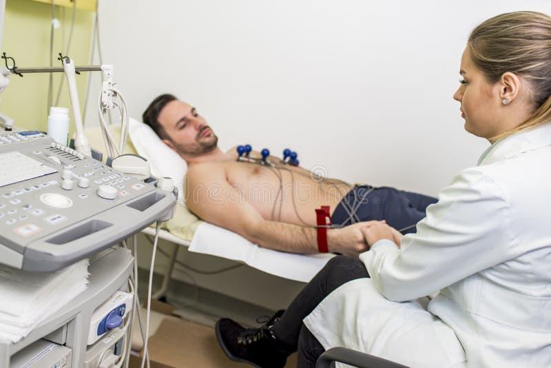 Hombre joven que hace ECG en hospital imagenes de archivo