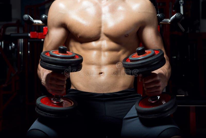 Hombre joven que hace ejercicio pesado en gimnasio imagen de archivo libre de regalías