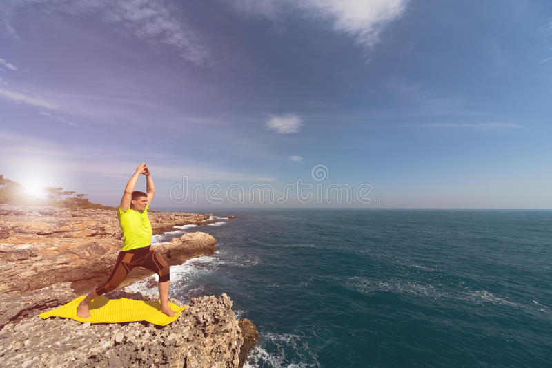 Hombre joven que hace ejercicios de la yoga fotos de archivo