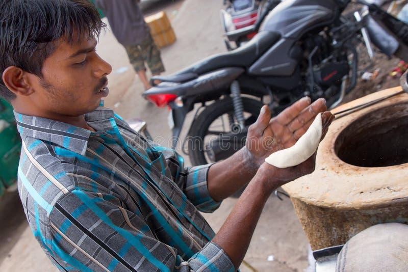 Hombre joven que hace el chapati en el restaurante del streetside en Delhi, Indi imagenes de archivo