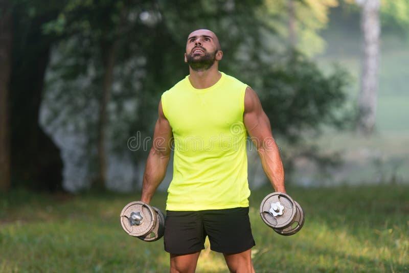 Hombre joven que hace el ejercicio para el entrenamiento del bíceps al aire libre foto de archivo