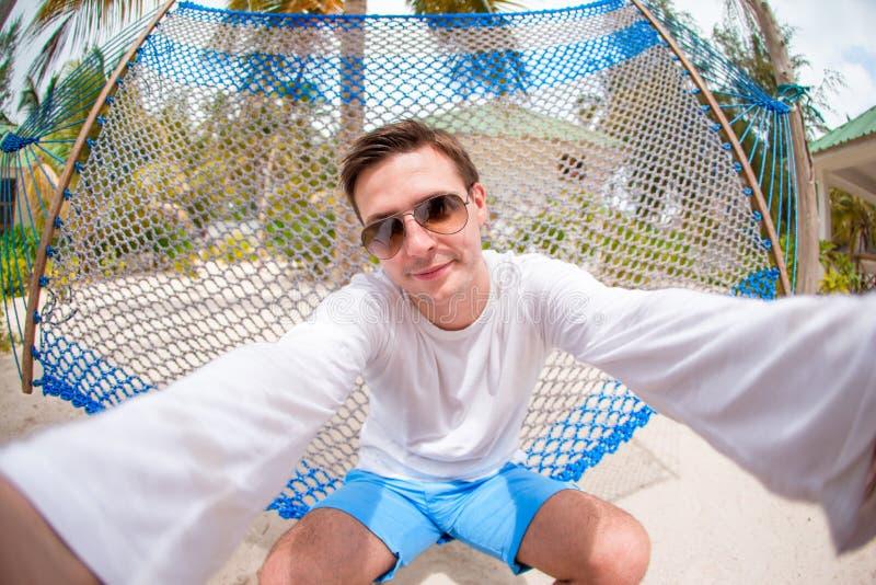 Hombre joven que hace el selfie que se relaja en la hamaca fotos de archivo