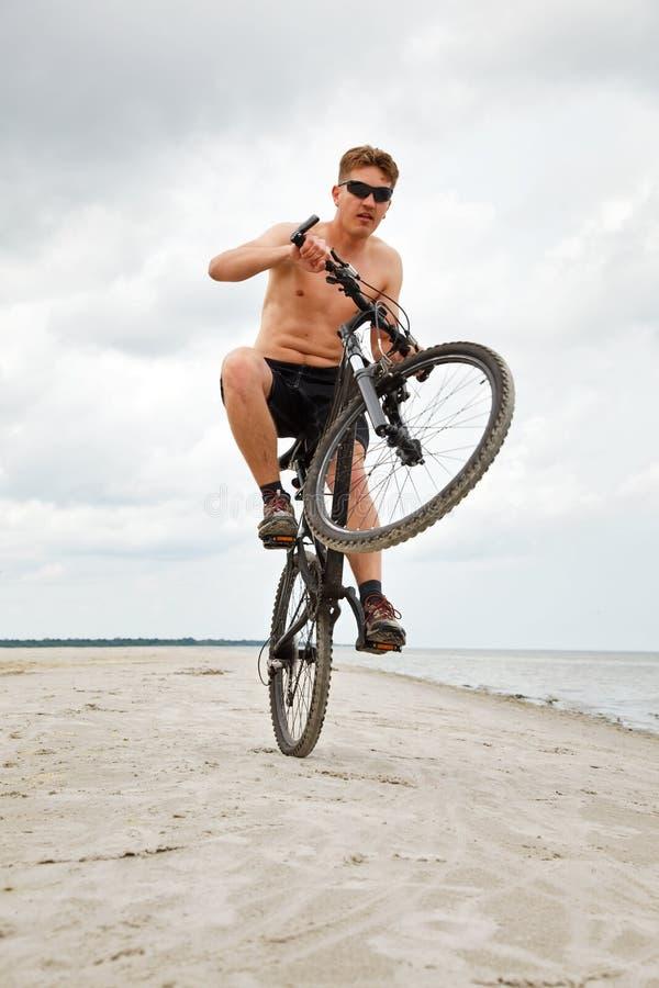 Hombre joven que hace el wheelie fotografía de archivo
