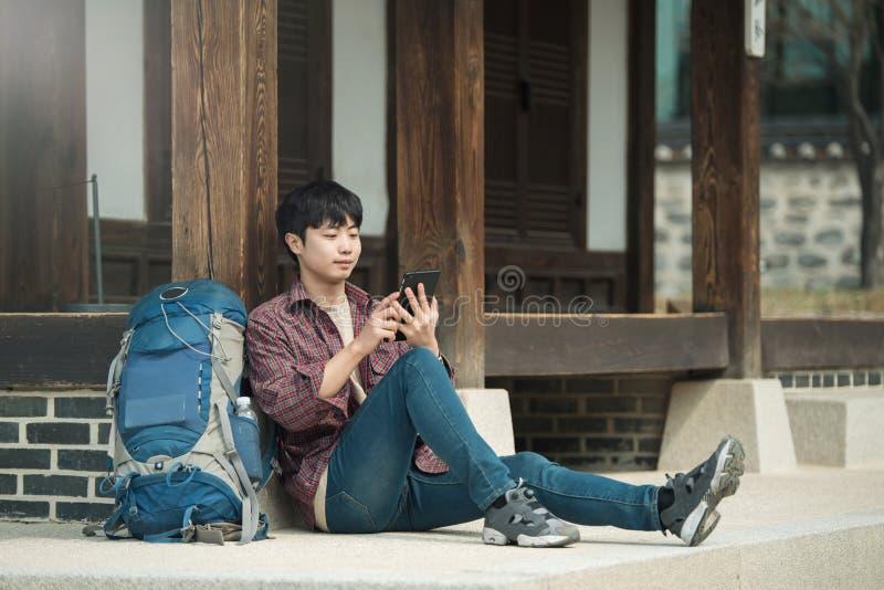 Hombre joven que hace excursionismo en Corea el sentarse en una casa tradicional coreana y usar una tableta fotografía de archivo