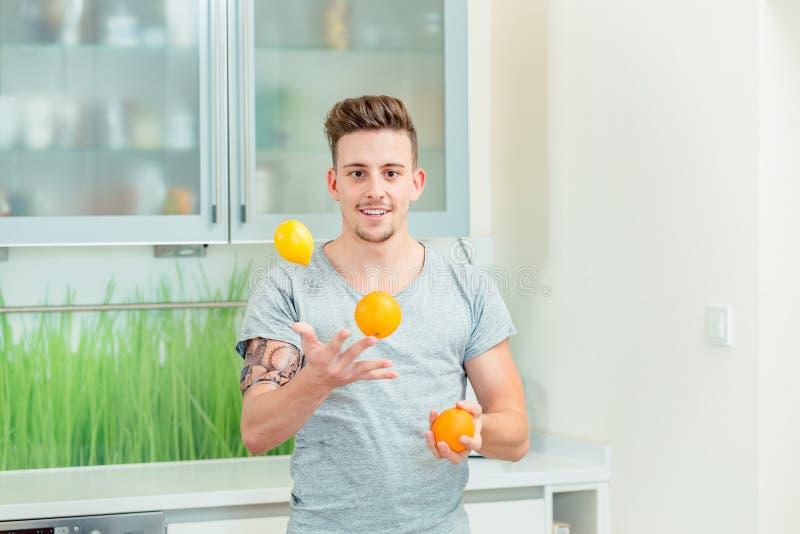 Hombre joven que hace juegos malabares con las naranjas frescas fotos de archivo libres de regalías