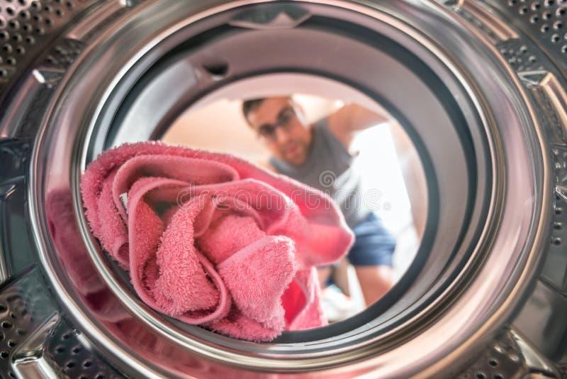 Hombre joven que hace la opinión del lavadero del interior de la lavadora foto de archivo
