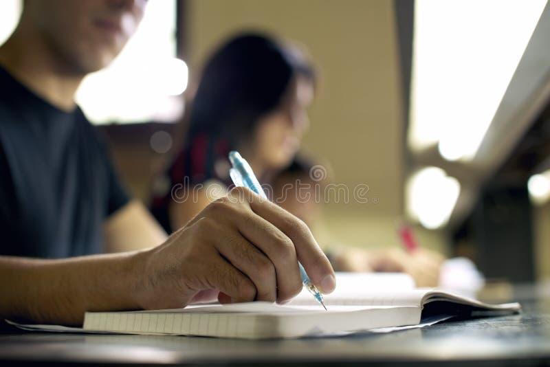 Hombre joven que hace la preparación y que estudia en biblioteca de universidad imagen de archivo libre de regalías