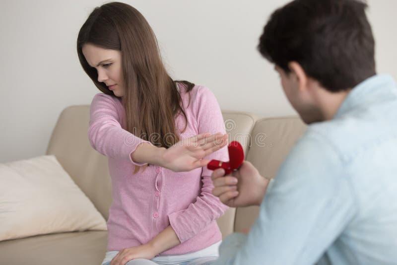 Hombre joven que hace la propuesta de matrimonio, anillo de compromiso, rechazo de la señora fotografía de archivo