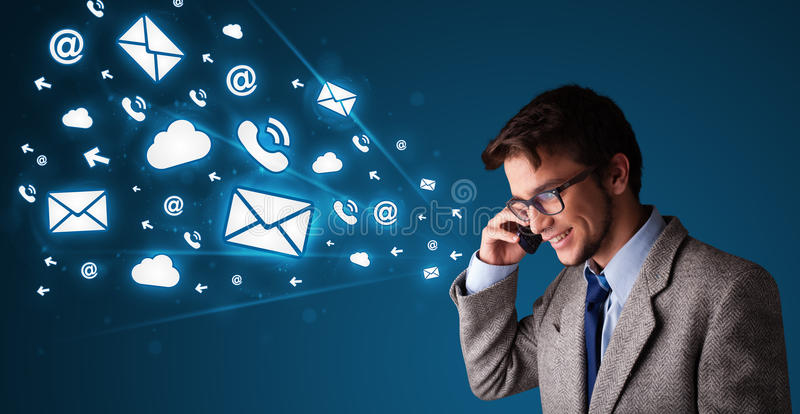 Hombre joven que hace llamada de teléfono con los iconos del mensaje imagen de archivo