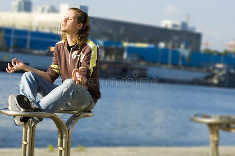 Hombre joven que hace movimientos de la yoga fotos de archivo