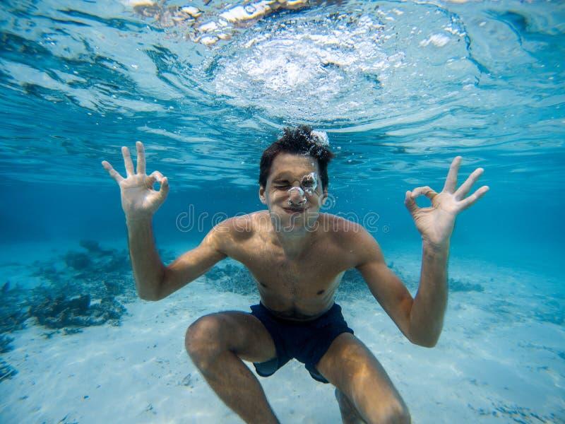 Hombre joven que hace muecas bajo el agua Agua azul clara foto de archivo