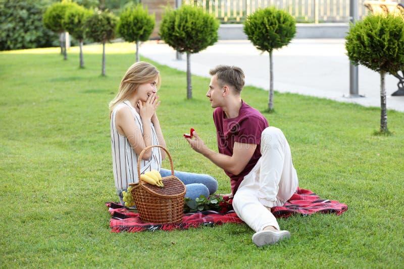 Hombre joven que hace oferta a su novia en fecha romántica en parque imagen de archivo