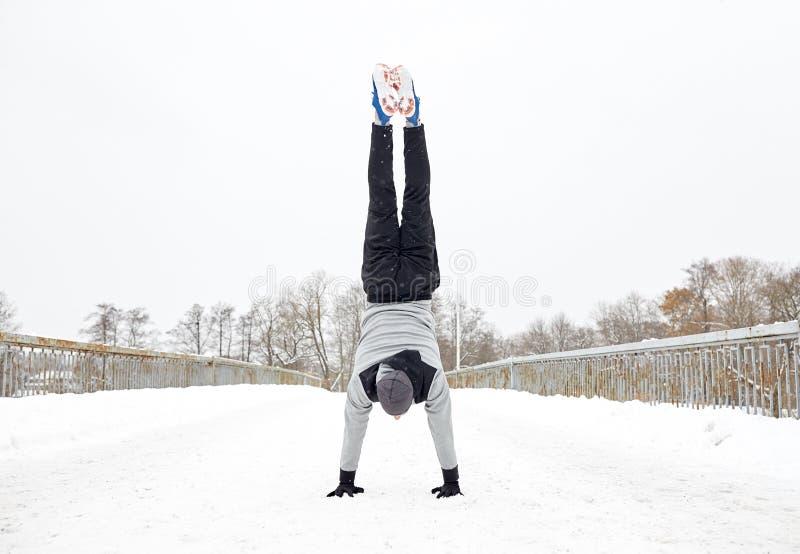 Hombre joven que hace posición del pino en invierno imagen de archivo libre de regalías